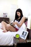 Hemmastadd avslappnande läs- tidskrift för lycklig kvinna i säng Arkivbild
