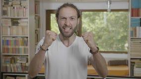 Hemmastadd fira seger för Overexcited ung hipster som ler och gör vinnande gest - arkivfilmer