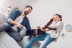 Hemmastadd flicka för fader som och för liten dotter spelar gitarren medan lyssna för fader som är gladlynt royaltyfri bild