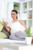 Hemmastadd gravid kvinnaläsebok arkivbild