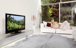 Hemmastadd hållande ögonen på TV Arkivbild