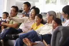 Hemmastadd hållande ögonen på TV för storfamiljgrupp tillsammans royaltyfri fotografi