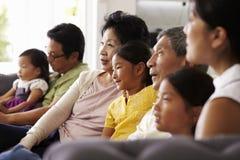 Hemmastadd hållande ögonen på TV för storfamiljgrupp tillsammans arkivbilder
