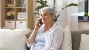 Hemmastadd hög kvinna som kallar på smartphonen stock video