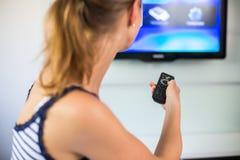 Hemmastadd hållande ögonen på TV för ung kvinna Fotografering för Bildbyråer