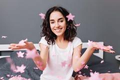 Hemmastadd komfort för lycklig älskvärd tid av den unga glade kvinnan i pyjamas med klippt lockigt hår som har gyckel i fallande  royaltyfri foto