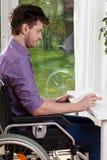 Hemmastadd läsning för rörelsehindrad man en bok Arkivfoton