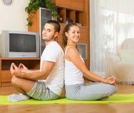 Hemmastadd praktiserande yoga för par Royaltyfri Bild