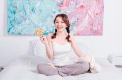 Hemmastadd pyjamas för gladlynt lycklig ung flicka med flätade råttsvansar royaltyfria foton
