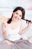 Hemmastadd pyjamas för gladlynt lycklig ung flicka med flätade råttsvansar royaltyfri fotografi