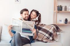 Hemmastadd sammanträdeflicka för fader som och för liten dotter kramar le för tidning för fader läs- royaltyfri foto