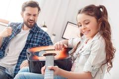 Hemmastadd sammanträdeflicka för fader som och för liten dotter spelar den sjungande gitarrfadern arkivfoton