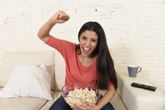 Hemmastadd soffasoffa för kvinna som håller ögonen på den upphetsade tvfotbollsporten fira seger Arkivfoton