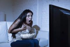 Hemmastadd soffasoffa för latinsk kvinna i film för fasa för television för vardagsrum hållande ögonen på läskig eller spänningth Royaltyfri Bild