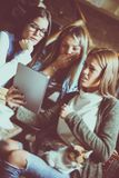 Hemmastadda flickor hålla ögonen på något chocka på minnestavlan och mummel arkivfoto