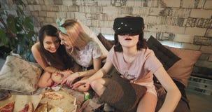 Hemmastadda partidamer i pyjamas som tillsammans spenderar en bra tid en av flickan som använder en VR som undersöker nya teknike stock video