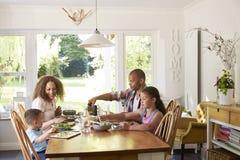 Hemmastatt ätamål för familj i kök tillsammans royaltyfri bild