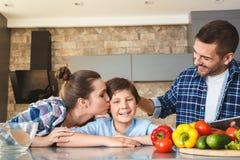 Hemmastatt anseende för familj i för kök som modern tillsammans kysser sonen medan fader som trycker på hans tillfredsställda lov royaltyfri fotografi