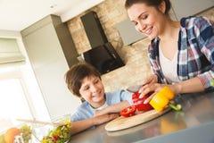 Hemmastatt anseende för familj i för kök som sonen tillsammans ser modern som klipper glade grönsaker arkivbild