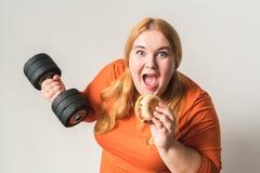 Hemmastatt anseende för knubbig kvinnasport som isoleras på den vita hållande hanteln som äter den gladlynta hamburgaren royaltyfri fotografi