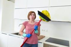 Hemmastatt kök för tjänste- kvinna i handskar som bär den frustrerade lokalvårdkvasten och golvmoppet Arkivbild