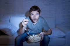 Hemmastatt ligga för ung attraktiv man på popcorn för tv för soffa som hållande ögonen på hållande bowlar att äta Arkivbild