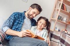 Hemmastatt sammanträde för fader som och för liten dotter kramar den lyckliga läseboken royaltyfria bilder