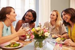 Hemmastatt sammanträde för kvinnliga vänner runt om tabellen för matställeparti royaltyfria foton