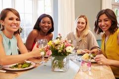 Hemmastatt sammanträde för kvinnliga vänner runt om tabellen för matställeparti royaltyfria bilder