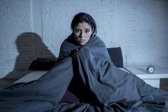 Hemmastatt sovrum för latinamerikansk kvinna som sent ligger i säng på natten som försöker att sova lidandesömnlöshet royaltyfri fotografi