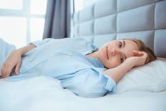 Hemmastatt vaknade lägga för ung kvinna i säng upp sömnigt royaltyfri fotografi