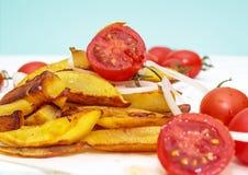 Hemmet gjorde potatismat med tomater körsbär och lök på kraft papper royaltyfri foto