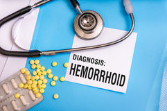 Hemorrhoid word written on medical blue folder. With patient files, pills and stethoscope on background royalty free stock image