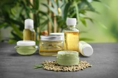 Hemp cosmetic products and seeds. On grey background Royalty Free Stock Photo