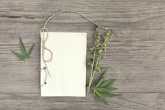 Hemp leaves and flowers with handmade craft notebook on old grunge wooden background. Top view. Minimalistic mockup. stock photo