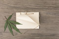 Hemp leaves and flowers with handmade craft notebook on old grunge wooden background. Top view. Minimalistic mockup. royalty free stock photos