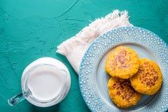 Hemp milk and pumpkin pancakes on a turquoise background. Horizontal royalty free stock image