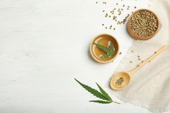 Hemp oil, seeds and space for text. On white wooden background, flat lay royalty free stock photos