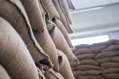 hemp sacks containing coffee bean in warehouse. stacked sacks in Stock Photography