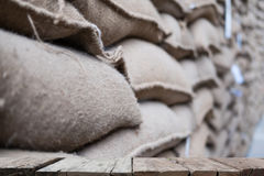 hemp sacks containing coffee bean in warehouse. stacked sacks in Stock Photos