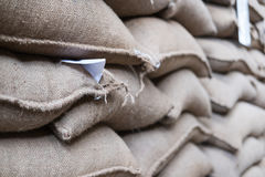 hemp sacks containing coffee bean in warehouse. stacked sacks in Stock Image