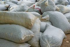 Hemp sacks full of harvest products accumulated on the ground. Agriculture, business concept Stock Photo