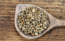 Hemp seed in spoon on table stock photos