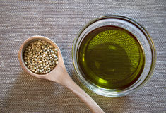 Hemp seeds and hemp oil. Healthy choice. Hemp seeds in the wooden spoon and hemp oil in the glass bowl Stock Photos