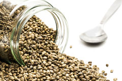 Hemp seeds in an overturned glass jar with spoon Royalty Free Stock Photo