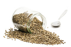 Hemp seeds in an overturned glass jar with spoon Stock Images