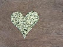 Hemp seeds shaped in heart symbol. Organic shelled hemp seeds shaped in a heart symbol Stock Photo