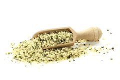 Hemp seeds. Wooden scoop with peeled hemp seeds isolated on white background royalty free stock images