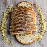 Hemp sourdough bread. Cut in fine slices on a wooden table royalty free stock photography