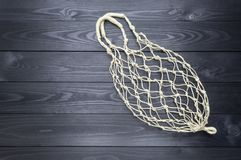 Hemp string bag on a dark wooden background. copy space royalty free stock photo